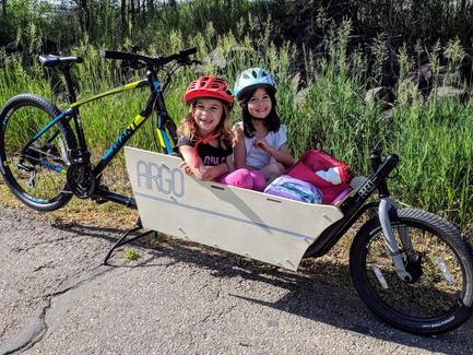 kids carried in a cargo attachment on an ebike