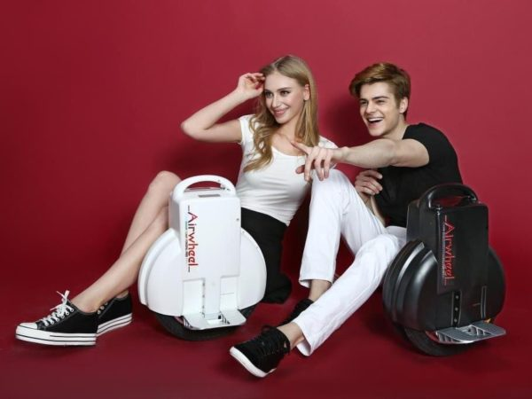 Girl and boy with airwheel unicycles