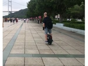 man rides electric unicycle