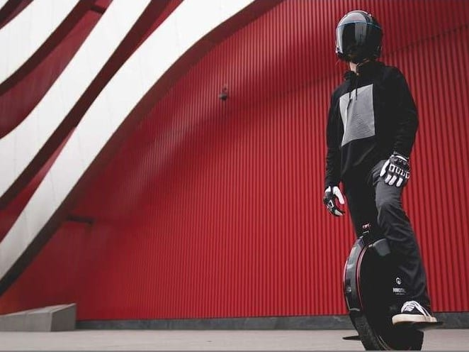 Inmotion electric unicycle man with helmet on